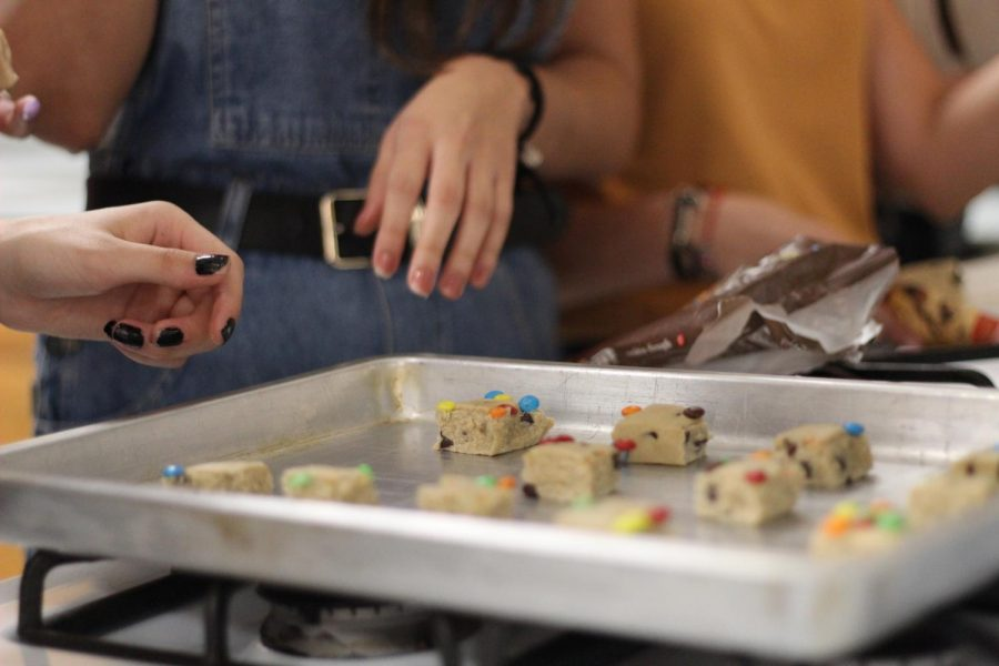 A student places M&M cookie dough chunks onto a cookie sheet during Cookies for Courage baking event on Sept. 10.